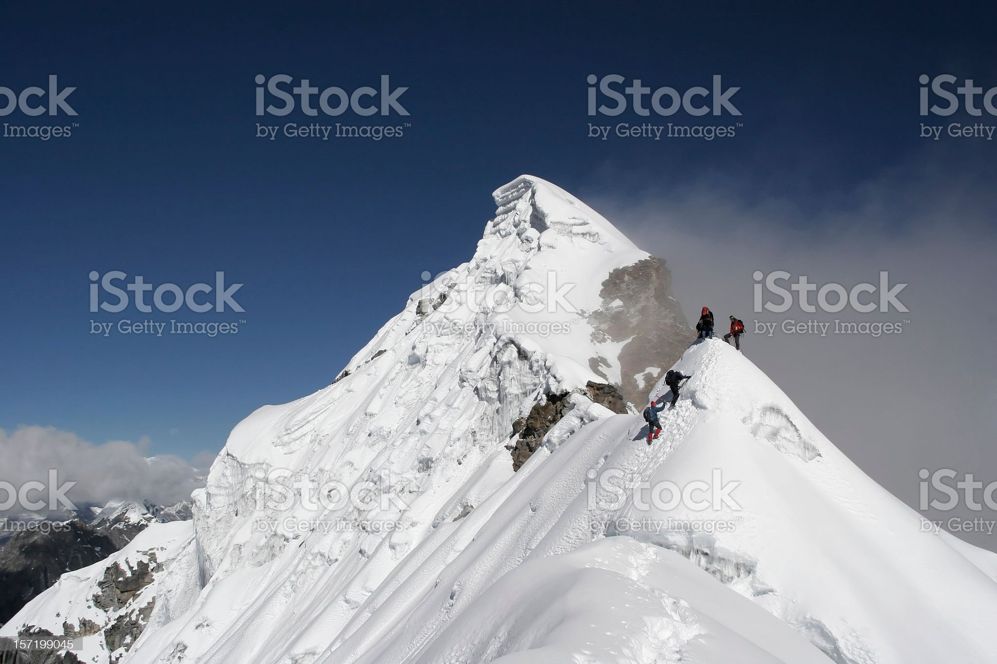 Two climbers almost at the top of a snowy mountain top royalty-free stock photo