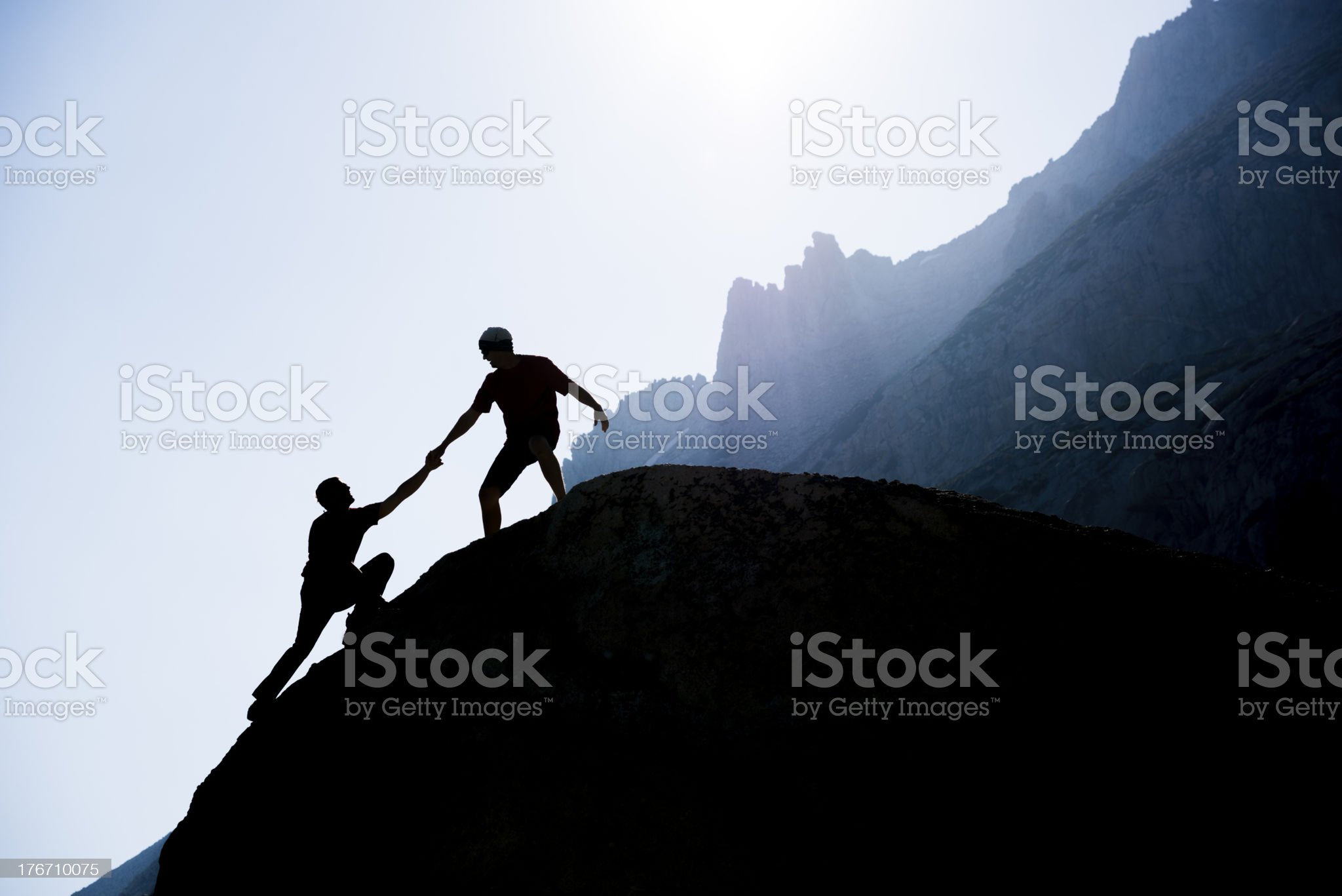 Two climbers reaching the top of a mountain royalty-free stock photo
