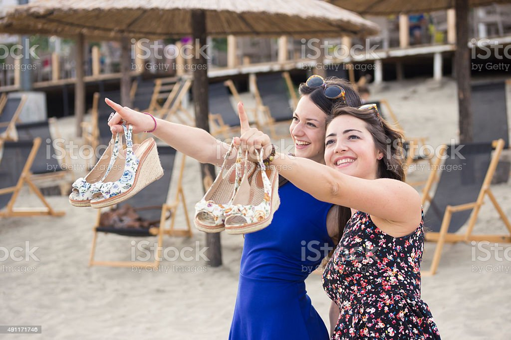 Two close friends, smilling and pointing up to sky. stock photo