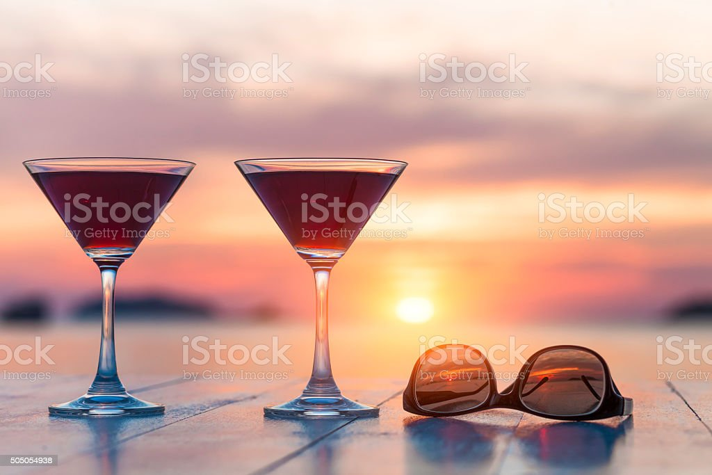 Two cocktails and sunglasses at a beach restaurant, honeymoon, sunset stock photo