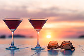 Two cocktails and sunglasses at a beach restaurant, honeymoon, sunset