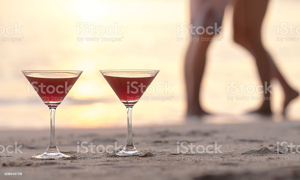 Two cocktails on the beach with couple kissing in background stock photo