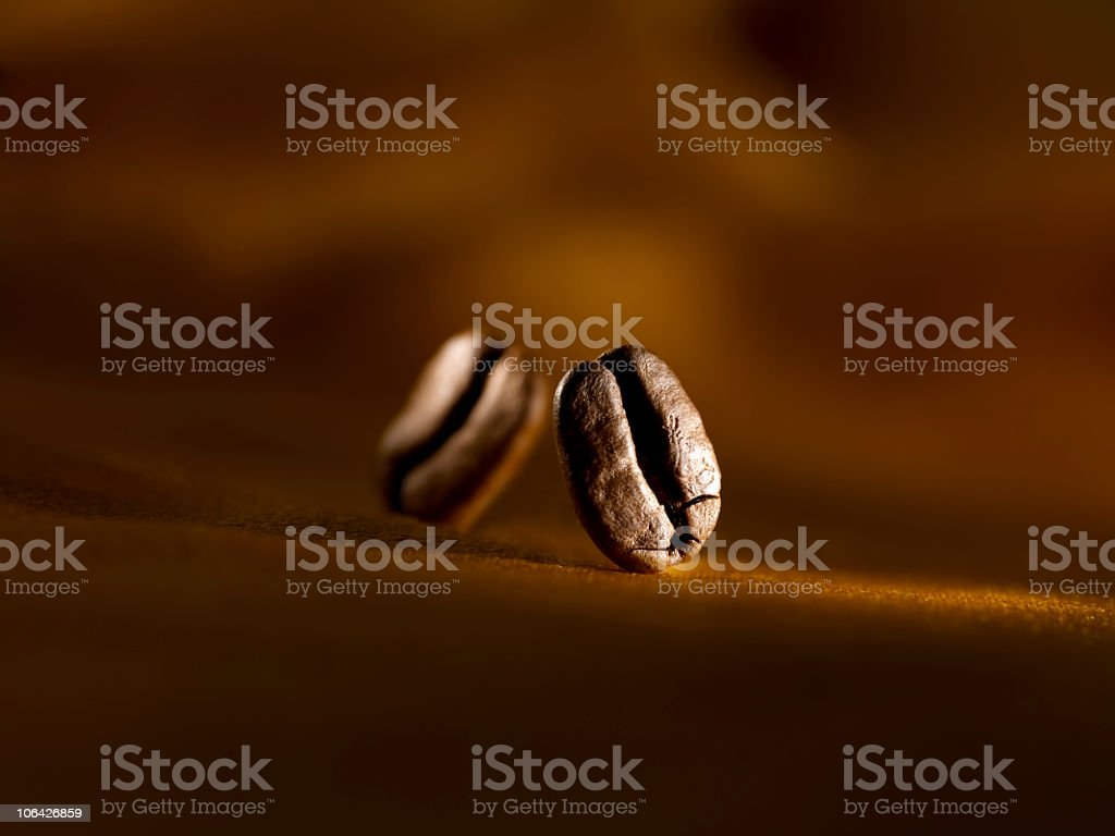 Two coffee beans landing on a brown surface royalty-free stock photo