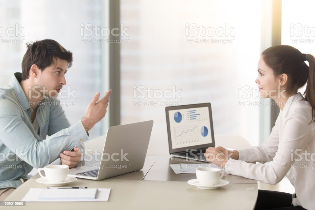 Two colleagues or partners discussing business issues sitting with laptops stock photo