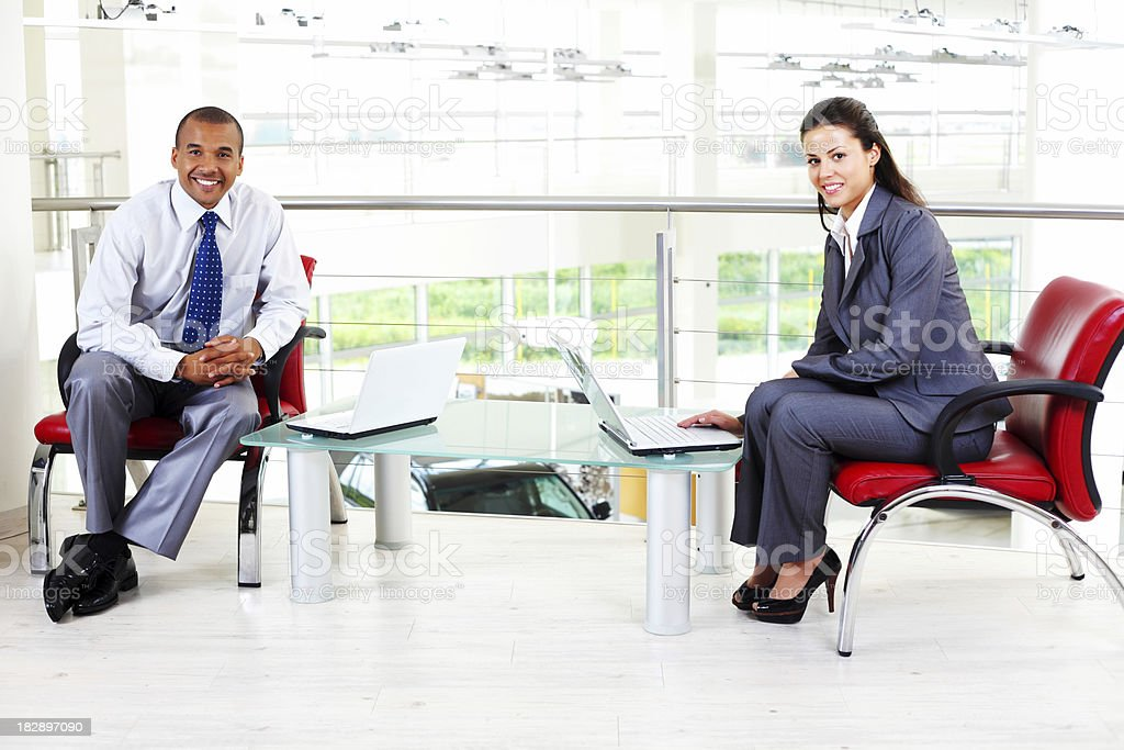 Two colleagues sitting in business building and looking at camer royalty-free stock photo