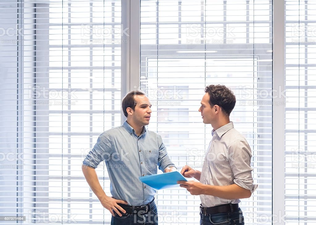 Two colleagues speaking together about project standing in bright office stock photo