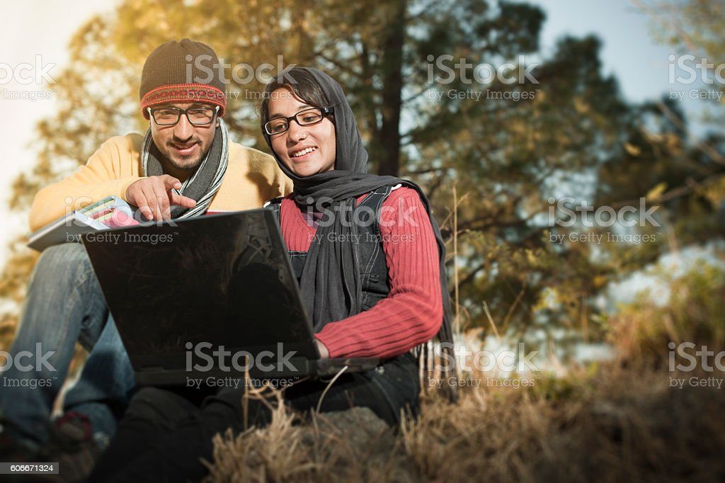 Two college students are using laptop together in hilly area. stock photo