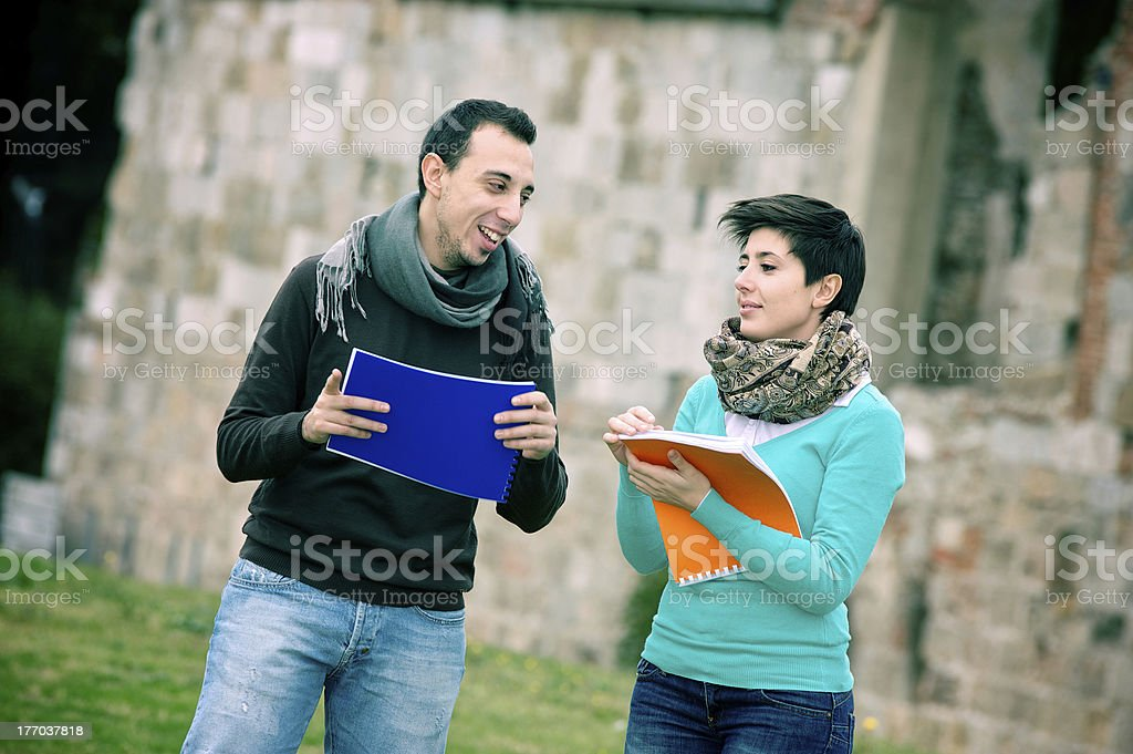 Two college students at park with books on hands royalty-free stock photo