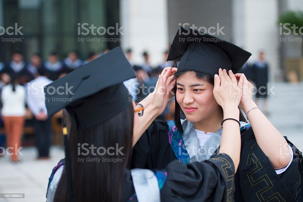 Two college students celebrate graduation stock photo