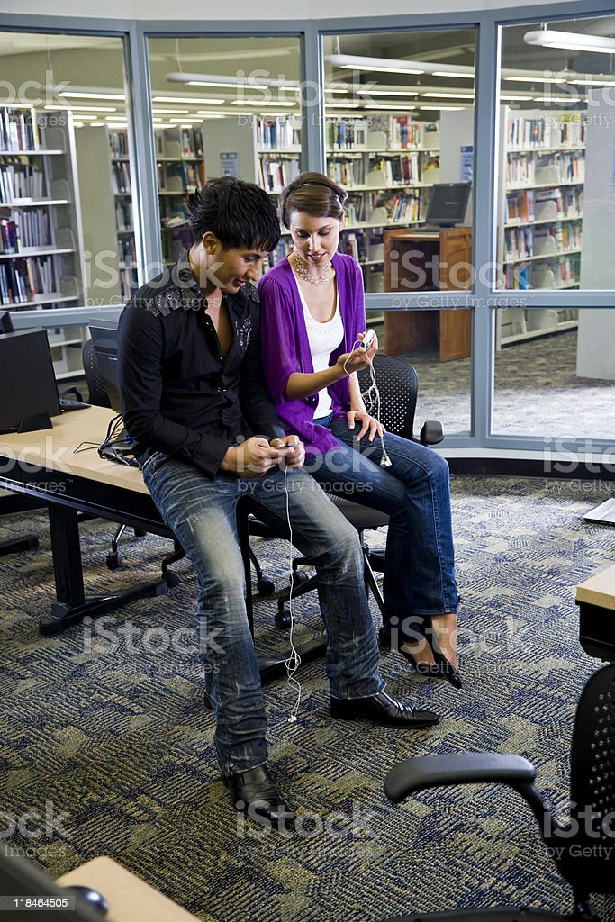 Two college students with music players in library stock photo