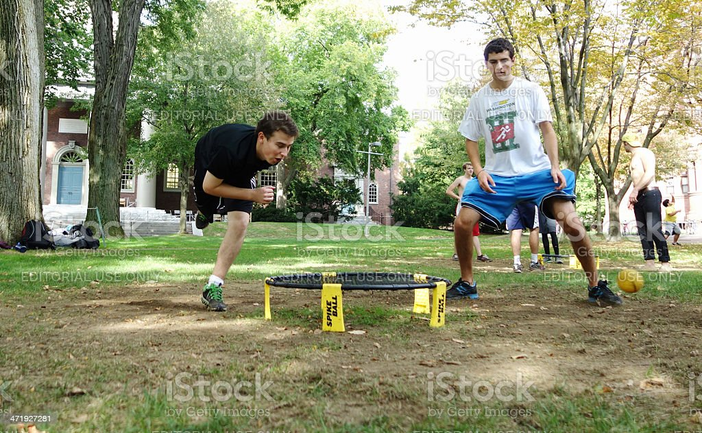 Two college-aged men playing spike ball stock photo