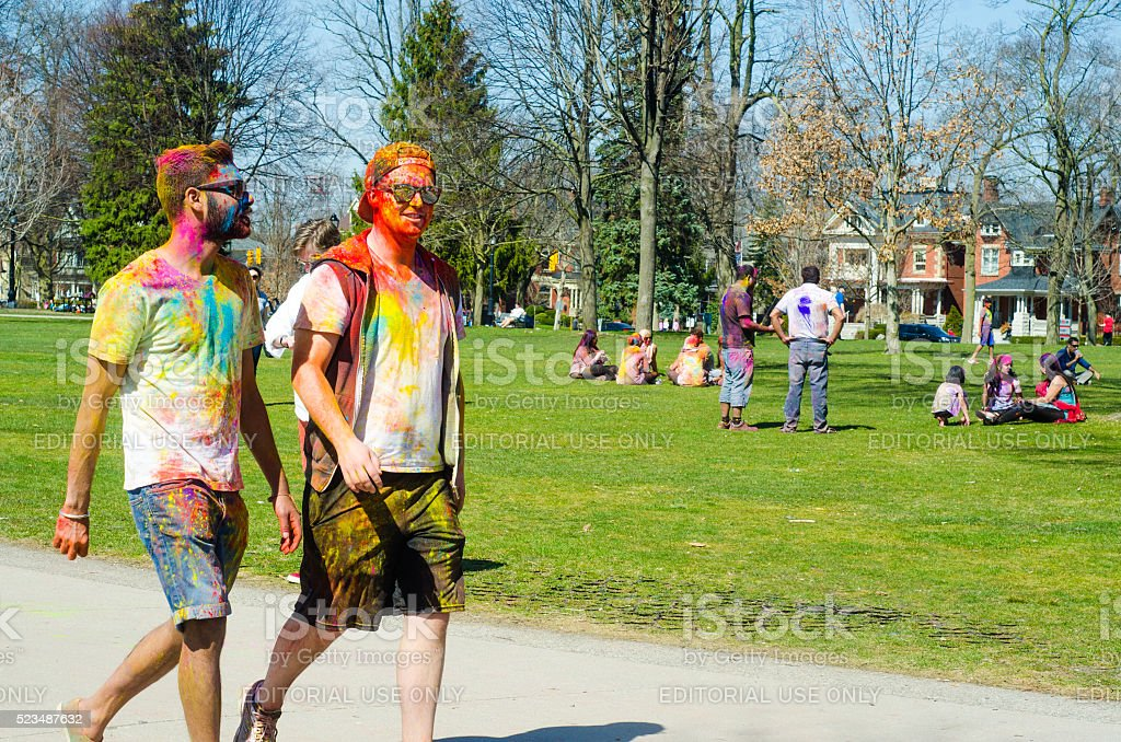 Two colorful boys walking in the park and celebrating Holi stock photo