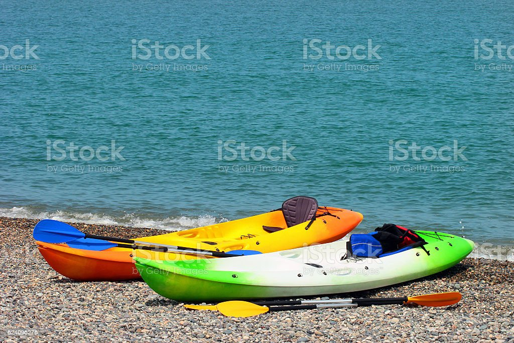 Two colorful sea kayaks with paddles and life jackets stock photo