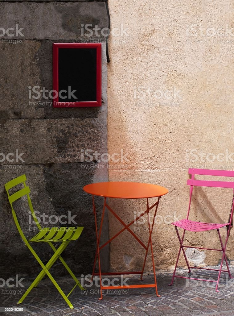 two colourful chairs and table at outside cafe in France stock photo