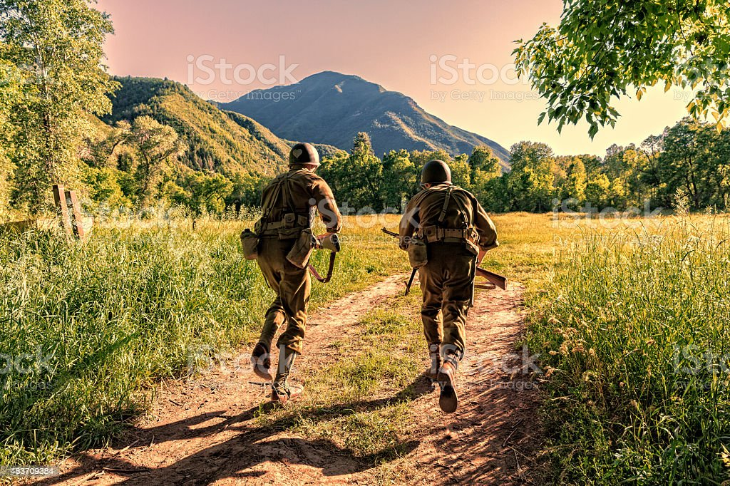 Two Combat Soldiers Take Off Running Across Open Field stock photo