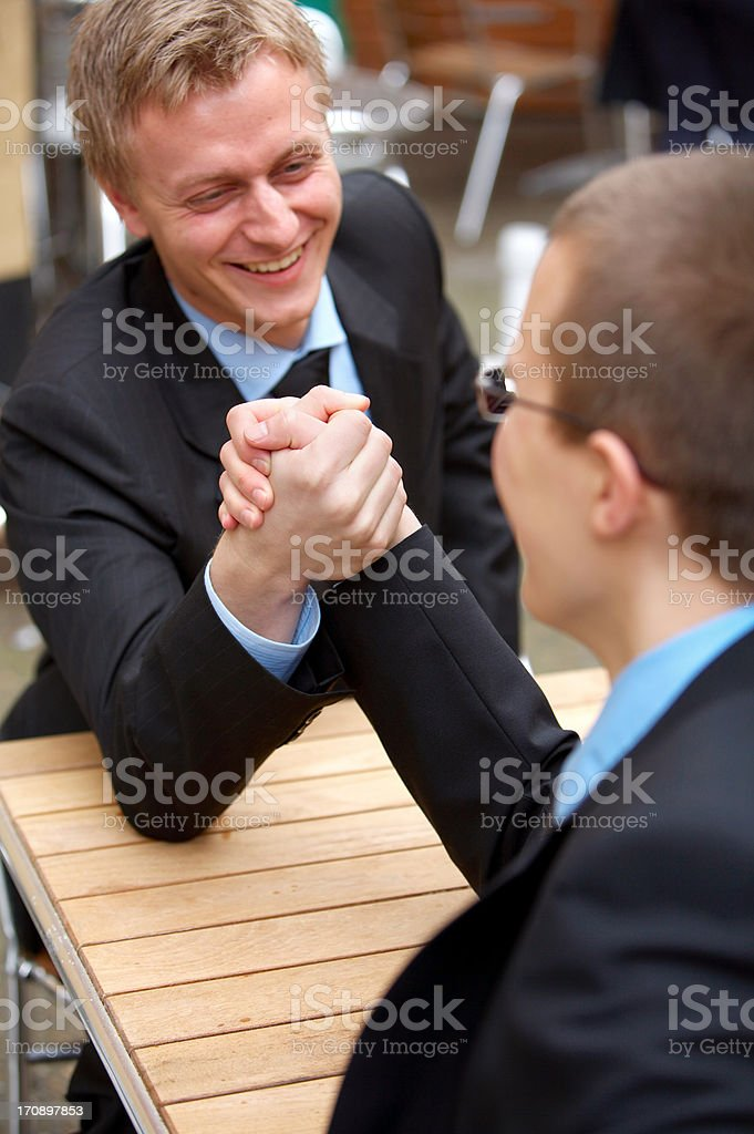 Two competing businessmen arm wrestling royalty-free stock photo