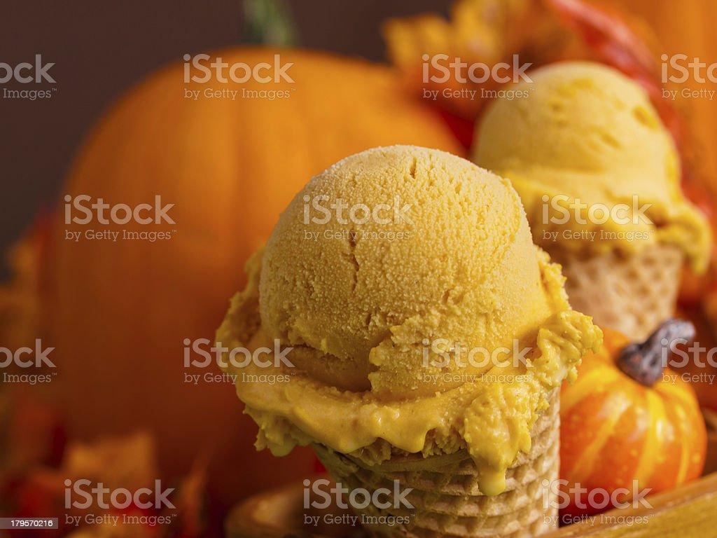 Two cones of pumpkin gelato and an orange pumpkin stock photo