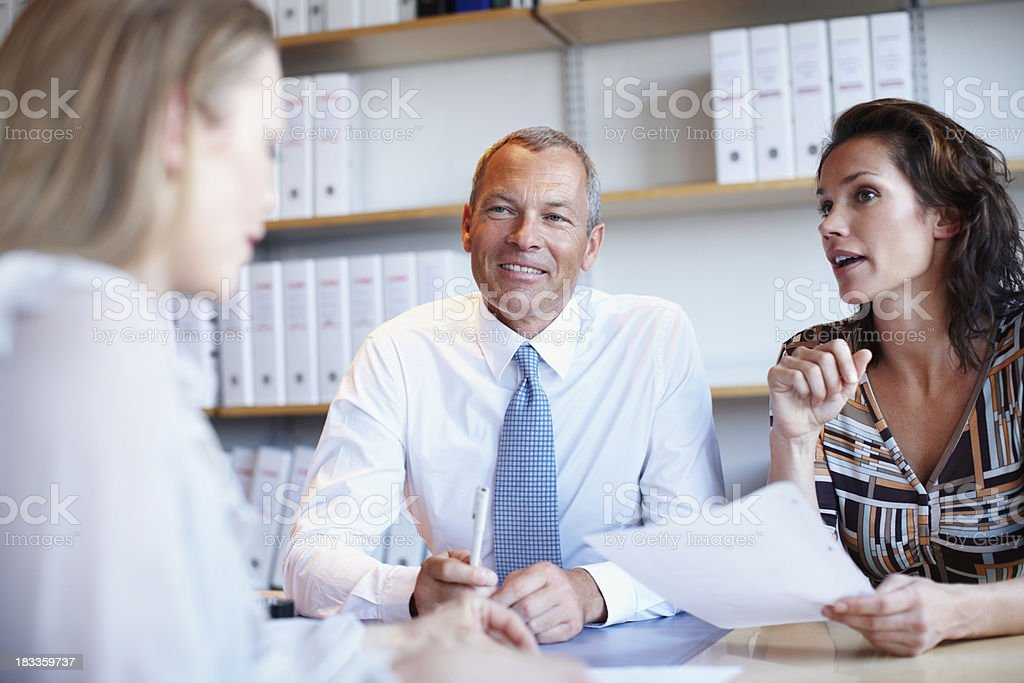 Two confident business people looking at woman during meeting royalty-free stock photo
