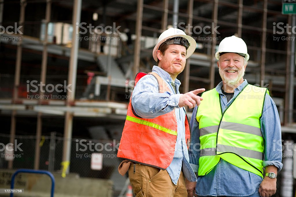 Two construction laborers talking royalty-free stock photo