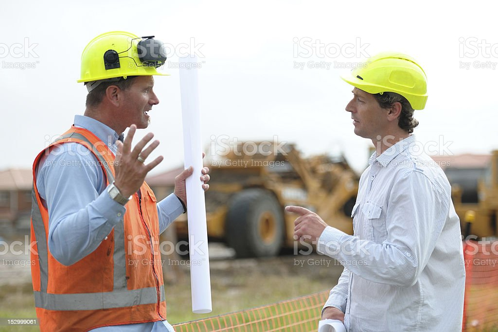Two construction workers arguing on either side of a pole royalty-free stock photo