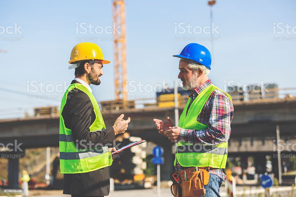 Two Construction Workers Discussing stock photo