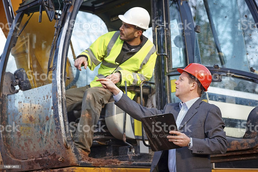 Male engineer explaining the work details to the earth mover driver...