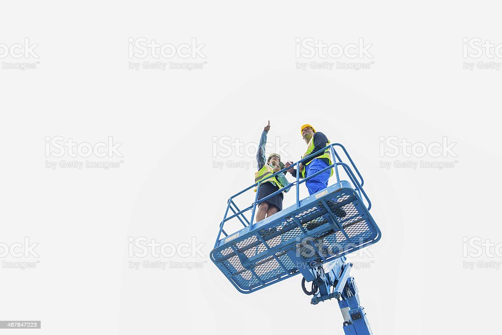 Two construction workers on a lifting ramp stock photo
