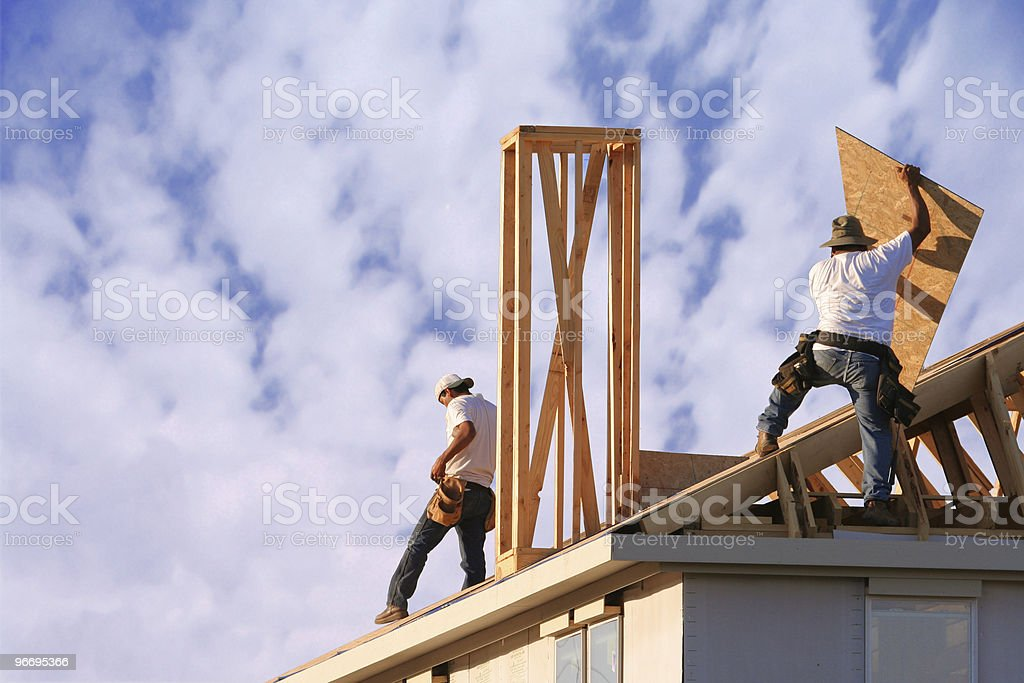 Two construction workers roof a new home royalty-free stock photo