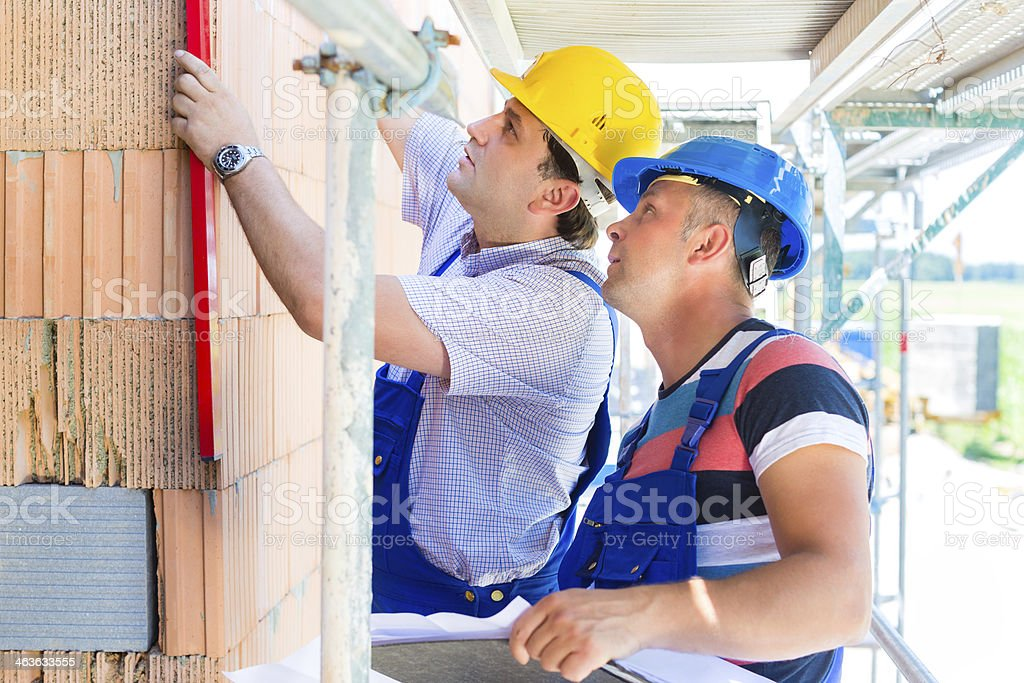 Two construction workers site checking the quality of work stock photo