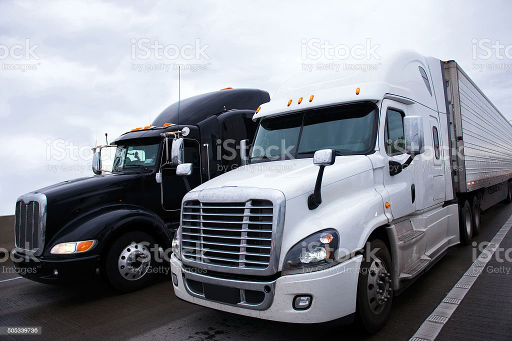 Two contrast modern semi truck different models black and white stock photo