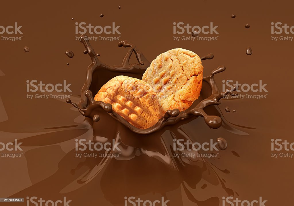 Two cookies biscuits falling into liquid chocolate splashing. stock photo