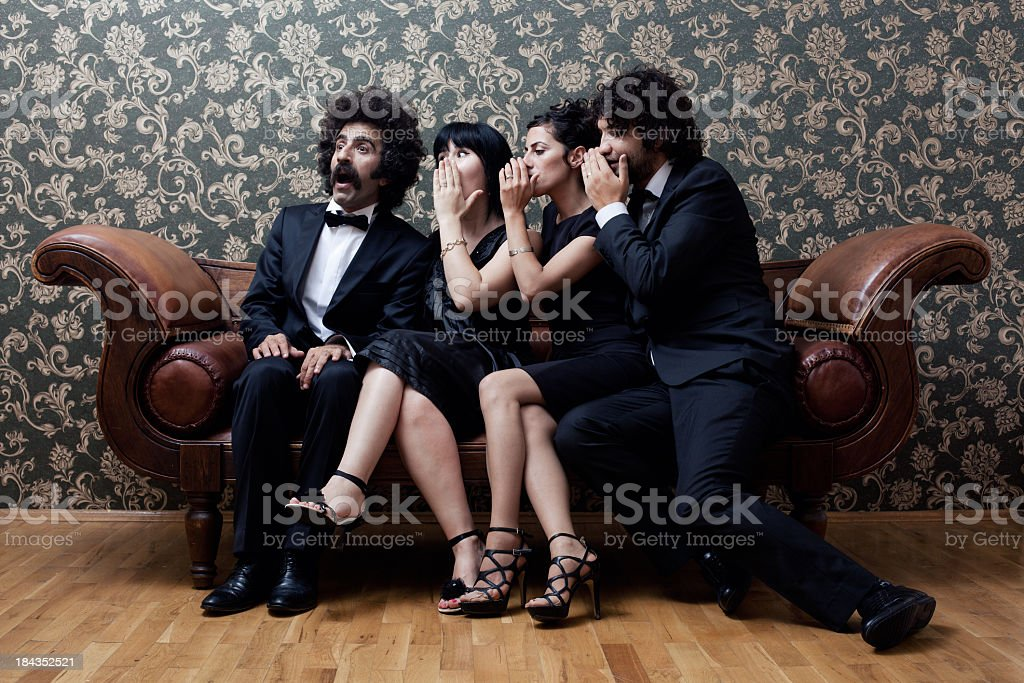 Two couples are sitting on sofa and whispering gossips stock photo