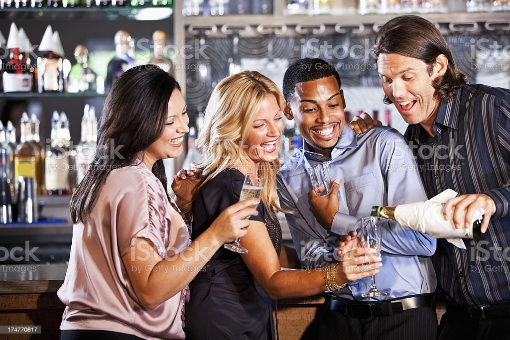 Two couples at bar pouring champagne stock photo