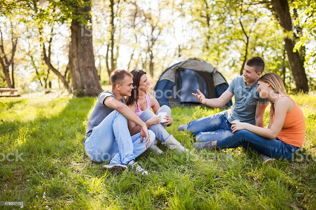 Two couples camping and talking to each other. stock photo