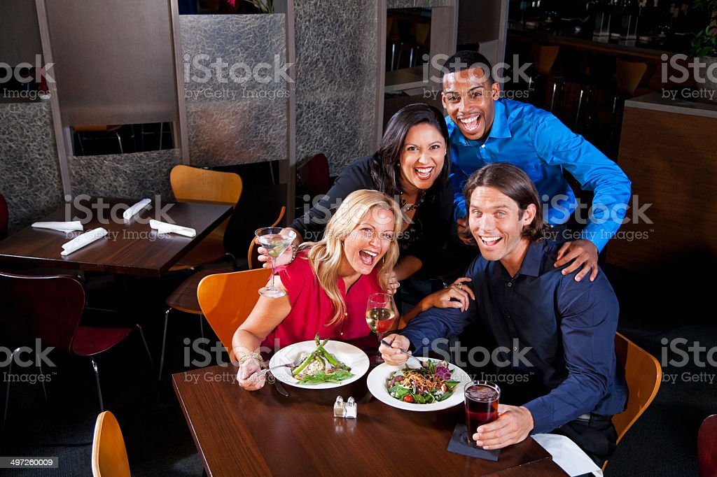 Two couples chatting in restaurant stock photo