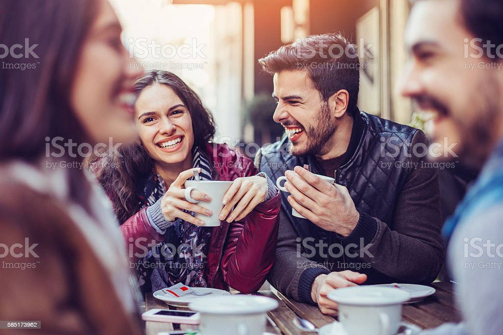 Two couples drinking tea and coffee stock photo