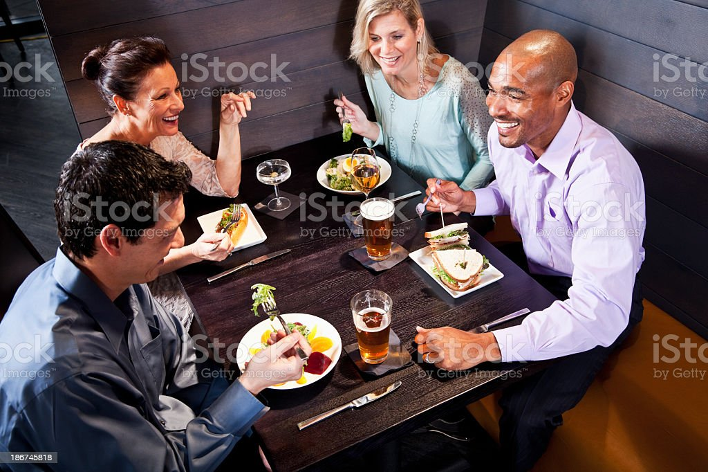Two couples eating in a restaurant stock photo