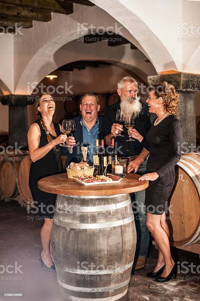 Two Couples Enjoying Food and Red Wine in Winery Cellar stock photo