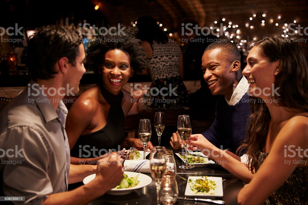Two Couples Enjoying Meal In Restaurant Together stock photo