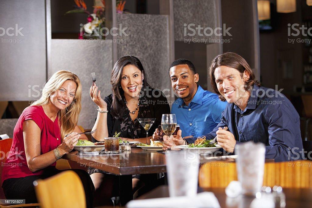 Two couples having dinner at restaurant stock photo