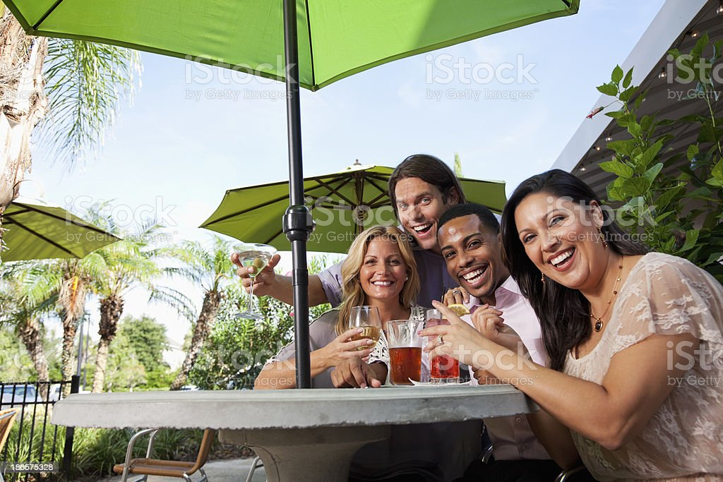 Two couples having drinks at outdoor cafe stock photo