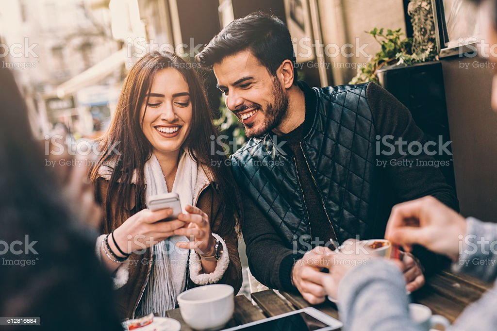 Two couples having fun in cafe outdoors stock photo