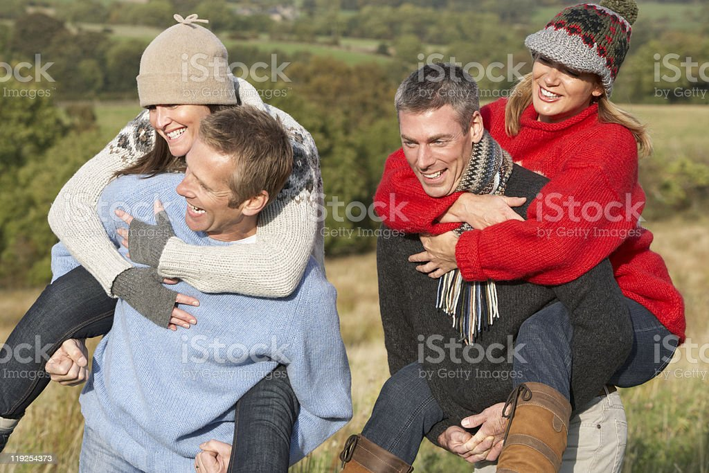 Two Couples Having Piggyback Ride In Autumn Landscape royalty-free stock photo