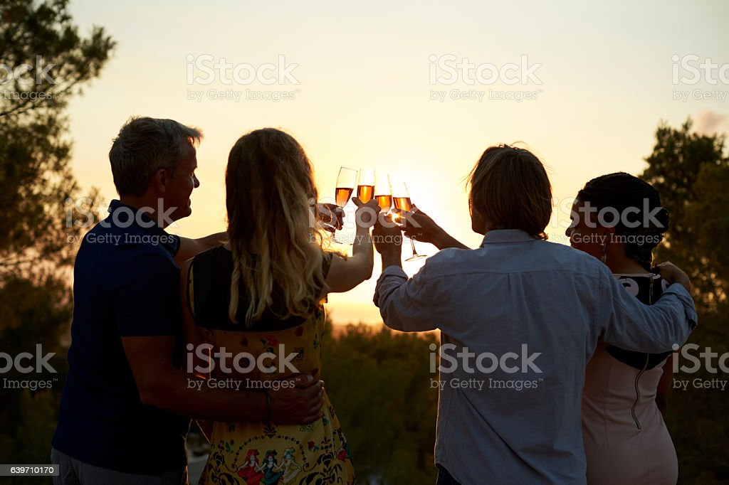 Two couples on a rooftop making a toast at sunset, stock photo