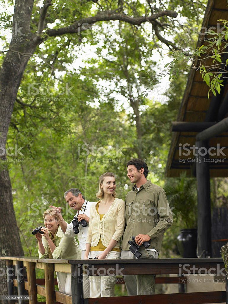 Two couples on balcony holding binoculars, smiling royalty-free stock photo