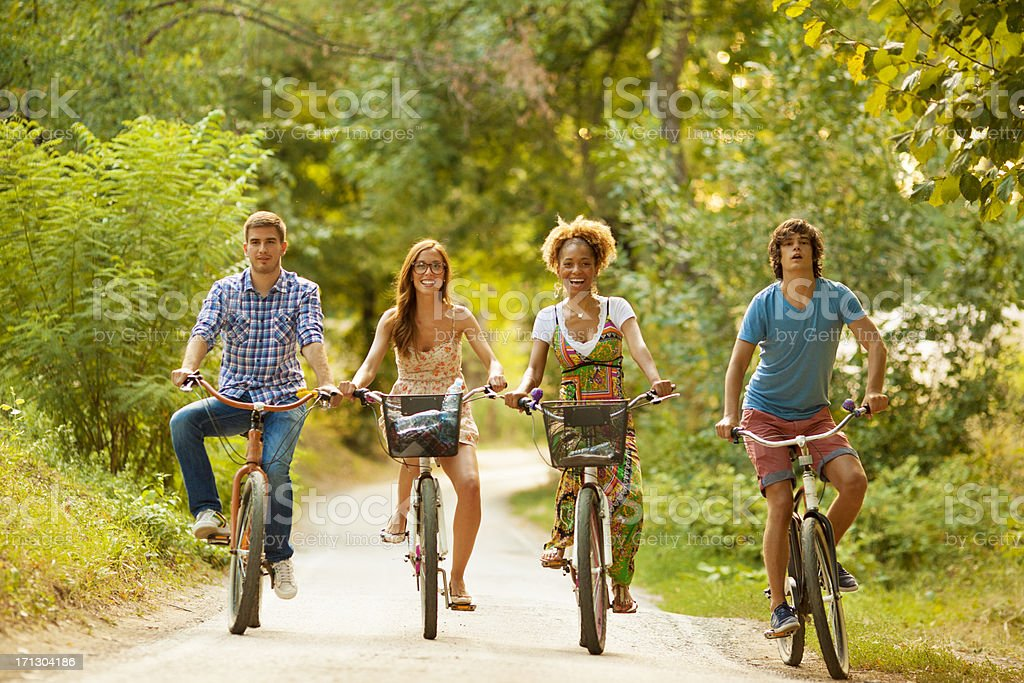 Two Couples Riding Bicycles in a park royalty-free stock photo