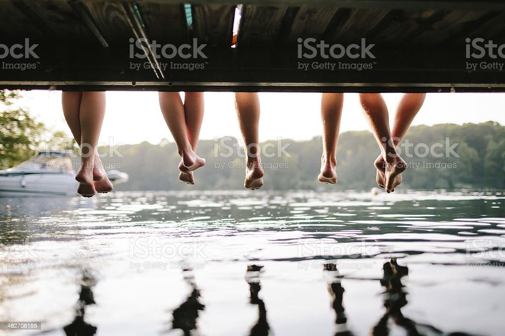 Two Couples Sitting On A Jetty stock photo