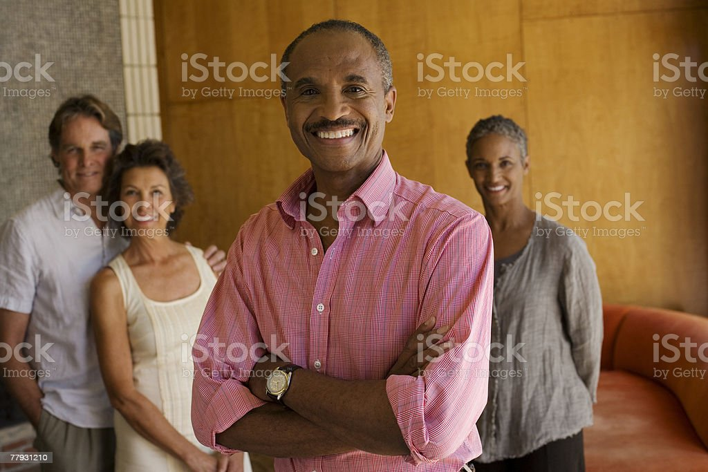 Two couples standing in modern home with one man in foreground stock photo