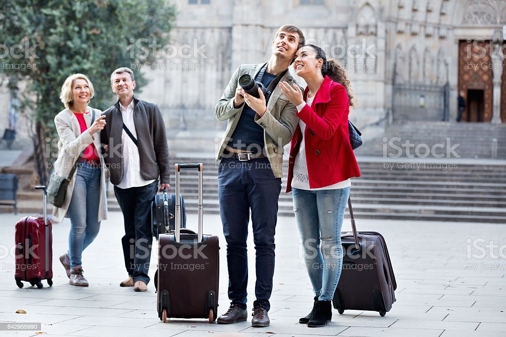Two couples with baggage sightseeing and smiling stock photo