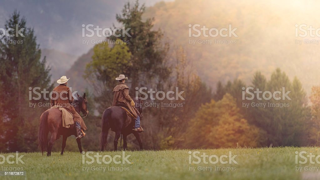 Two cowboys riding across a field in a forest stock photo